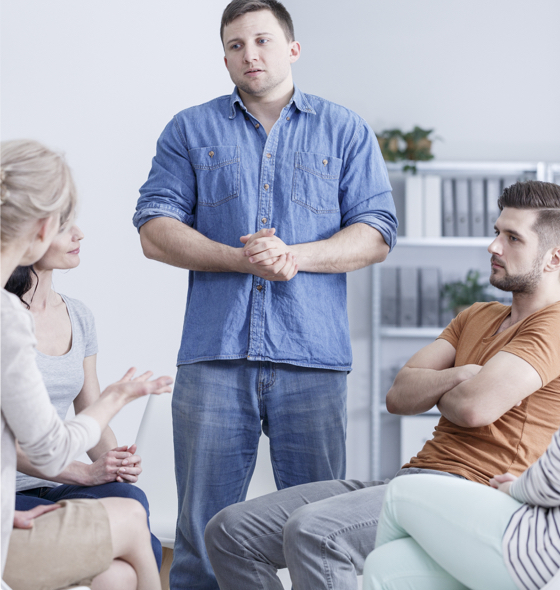 a group therapy session, a young boy wearing a jeans shirt talks about his experience