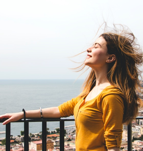 a woman in yellow top enjoying the wind while standing the balcony