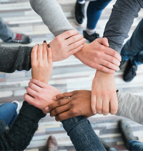 An image of 5 hands holding onto each others wrist