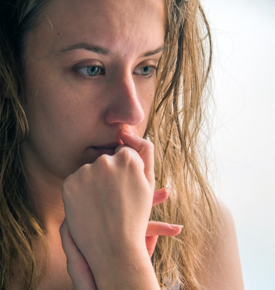 a woman looking down in thought, with both her hands interlocked gently placed on the mouth