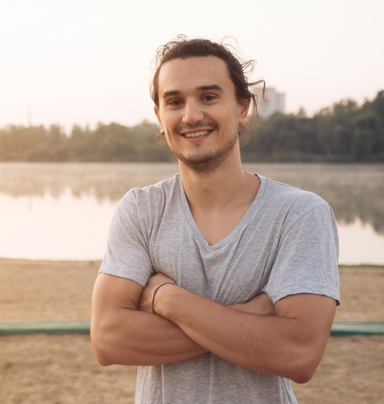 a young adult boy smiling, crossed hands, wearing grey t-shirt