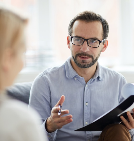 a therapist talking and explaining while holding a clipboard and a pen