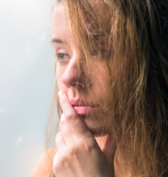 a young girl with messy hair looking outside the window in thought