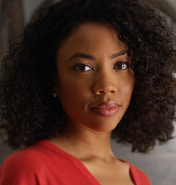 a dark-skinned woman who has curly hair wearing a red top giving a straight face pose